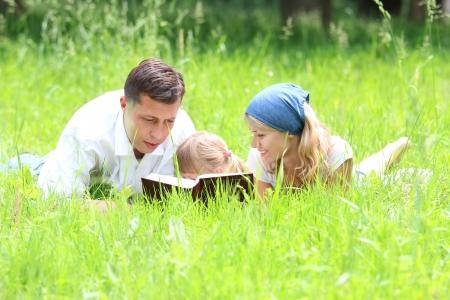 familia en la iglesia: familia joven con una hija joven lee la Biblia Foto de archivo
