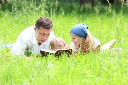 christian youth: young family with a young daughter reads the Bible
