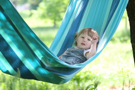 little girl on a hammock on nature photo