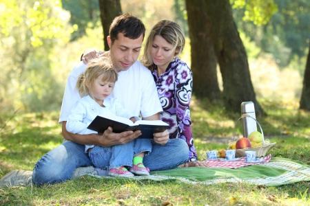 若い家族が自然の中で聖書を読む 写真素材