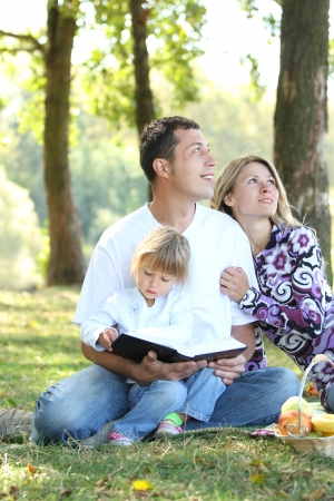 christian faith: young family read the Bible in nature Stock Photo