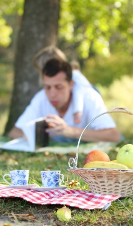 young father with baby daughter reading the Bible on a picnic photo