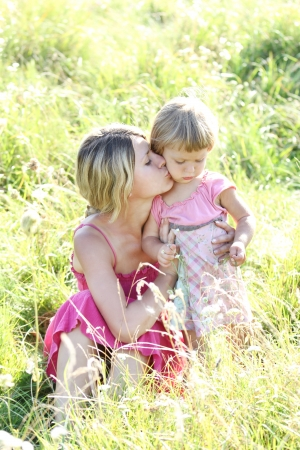 young mother and her little daughter on the grass outdoors photo
