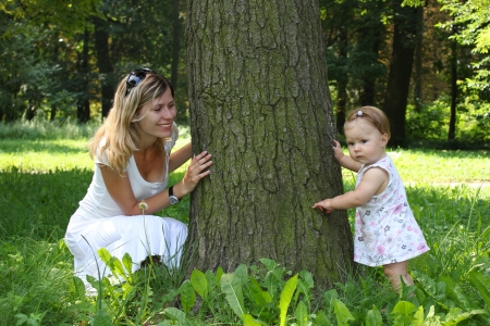 Mama and her little daughter play near the tree photo