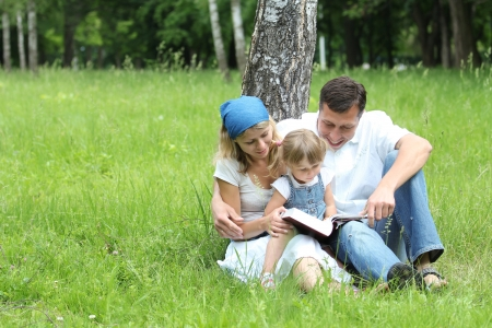 one parent: Young family reading the Bible in nature