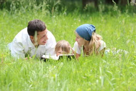 Young family reading the Bible in nature photo