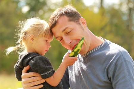 father and young daughter eat watermelon in nature photo