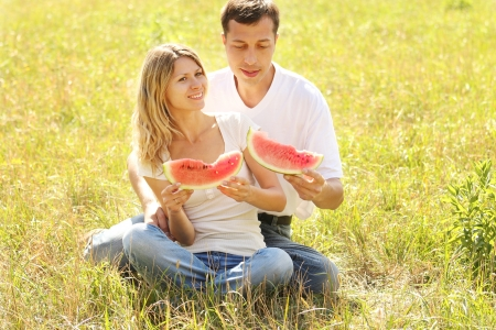 loving couple in nature eat watermelon photo