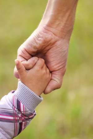 in custody: parent holds the hand of a small child Stock Photo