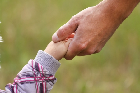 親は小さな子供の手を保持します。