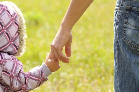 parent holds the hand of a small child photo