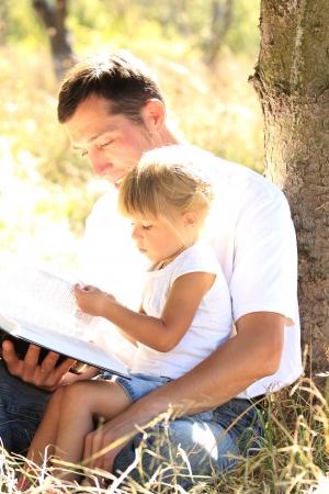 彼は小さな娘と若い父は聖書を読む