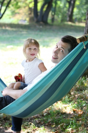 young father with his small daughter in a hammock photo
