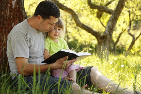 �glise: jeune p�re avec sa petite fille lit la Bible