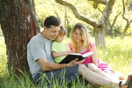 familia cristiana: Familia joven leyendo la Biblia en la naturaleza