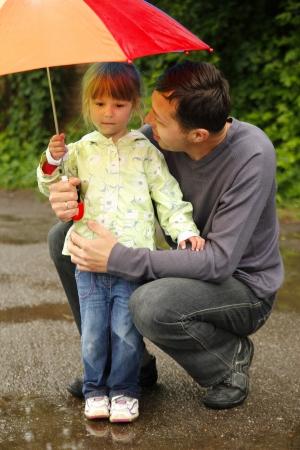 lluvia paraguas: ni�a con un paraguas bajo la lluvia con su padre Foto de archivo