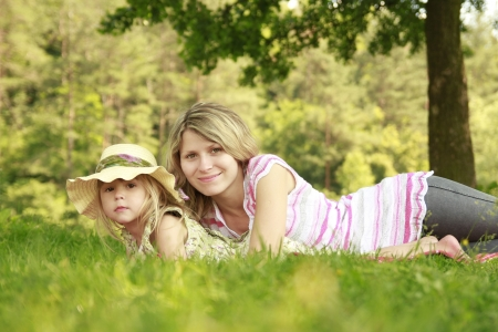 Mama and her little daughter  on grass photo