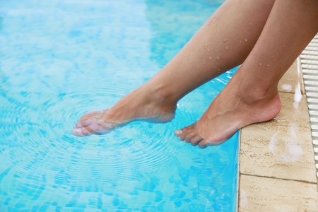 a female legs in the water pool photo