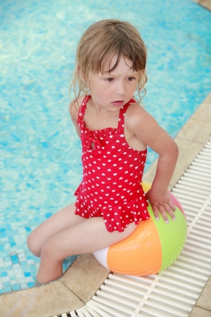 a little girl in the water pool with a ball photo