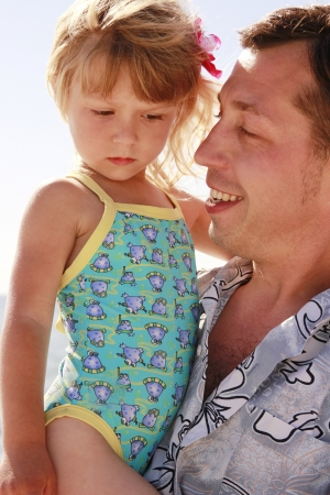Dad and little daughter playing on the beach photo