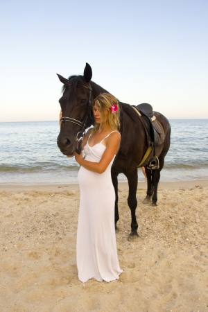 Girl with a horse by the sea photo