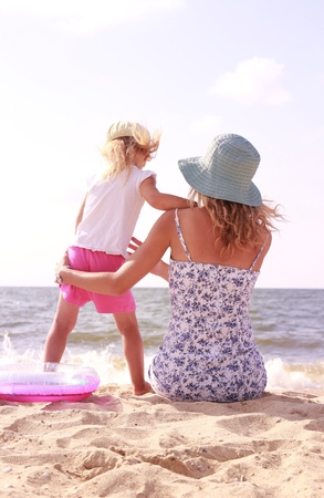 Mama and her little daughter playing on the beach photo