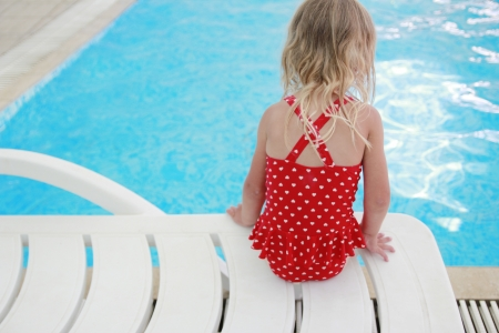little girl in the water pool on a sun lounger photo