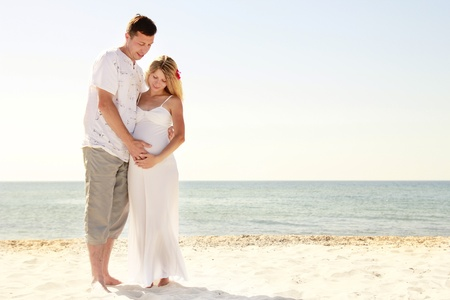 a Pregnant couple in love on the beach photo