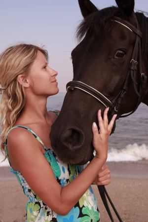 a Girl with a horse by the sea photo
