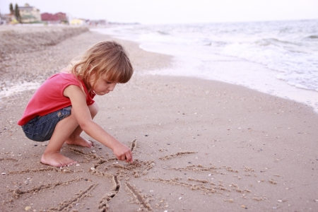 Little girl draws a sun in the sand on the beach photo
