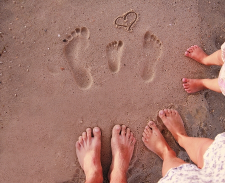 three objects: Family footprints in the sand on the beach