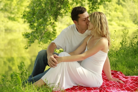 a A young pregnant couple on nature photo
