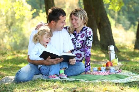自然の中で聖書を読んで若い家族 写真素材