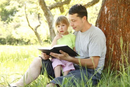 a young father with his little daughter reads the Bible photo