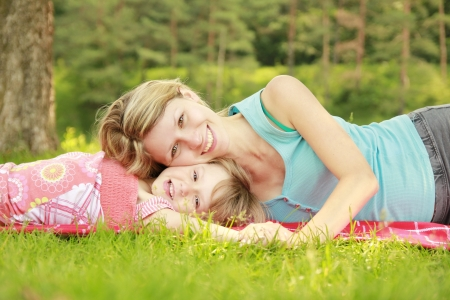 若い母親と彼女の小さな娘、芝生で遊んで