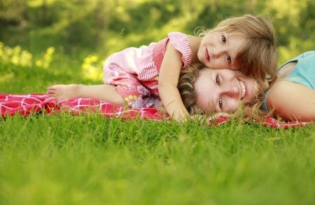 a young mother and her little daughter playing on grass