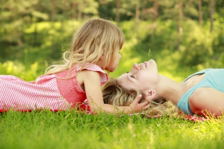 a young mother and her little daughter playing on grass photo