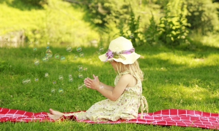 a little girl with soap bubbles photo