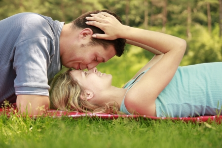 a couple in love outdoors lying on the grass photo