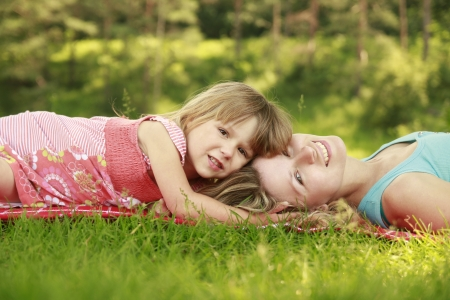 a mother playing with her little daughter on the grass photo