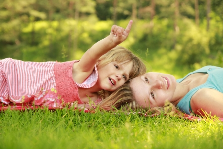 a mother playing with her ​​little daughter on the grass photo