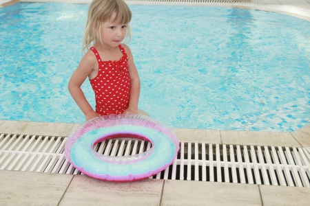 a girl swims in a pool with a circle photo