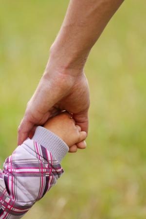niños caminando: uno de los padres tiene la mano de un niño pequeño Foto de archivo
