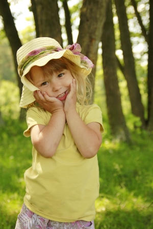a beautiful little girl in a hat on the nature photo