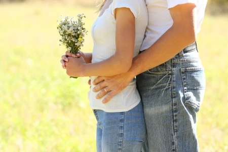 a Young beautiful couple in love with a bouquet of flowers in nature photo