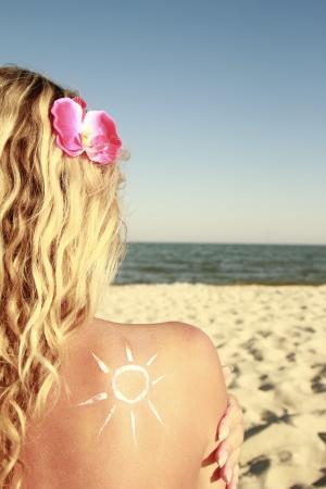 a of sun cream on the female back on the beach 写真素材