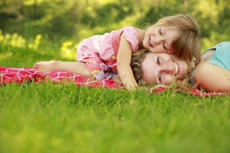 a Mama and her little daughter on the grass Stock Photo