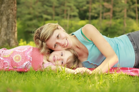a Mama and her little daughter on the grass  photo