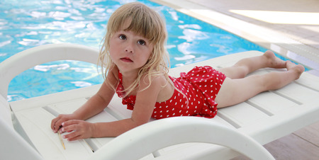 a little girl lying beside the pool photo