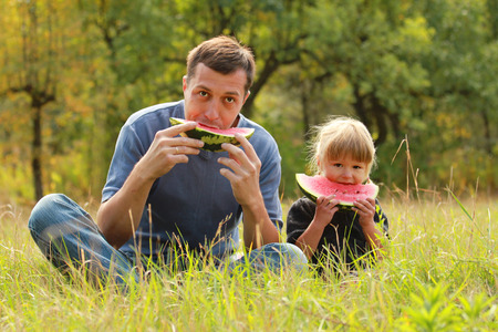 unity small flower: a father with a small daughter eat watermelon on the grass Stock Photo